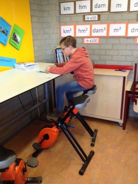 een jongetje die op een bureaufiets zit. Illustratief voor bewegend leren