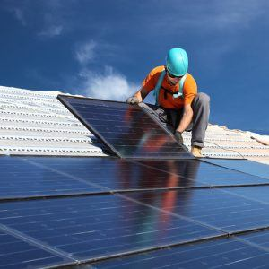 Man plaats zonnepanelen op een dak